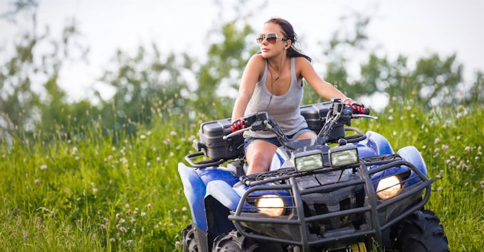 Girl riding ATV in a field